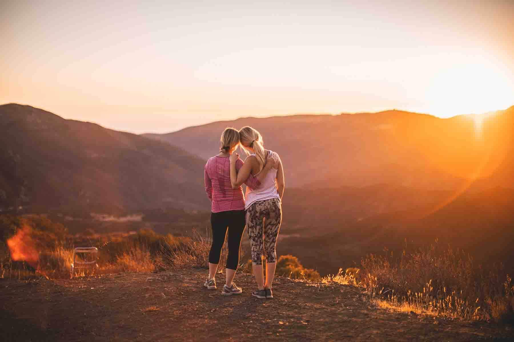 Two women looking at a sunset.