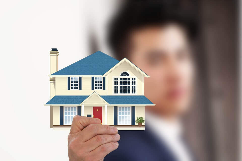 a man holding a picture of a house