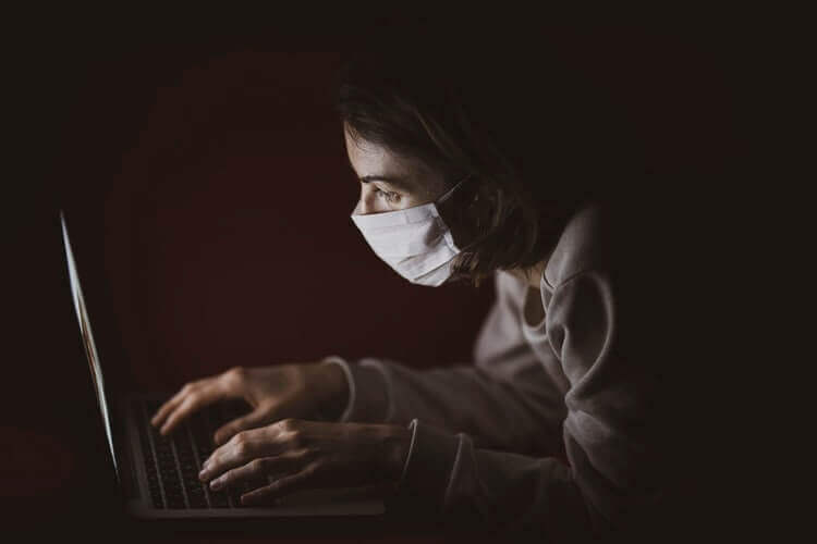 A woman wearing a mask browsing the internet