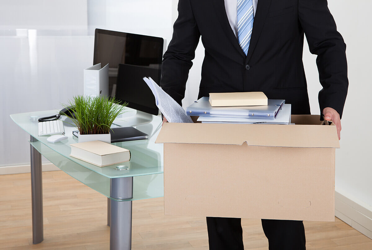 A person holding a box with office supplies.