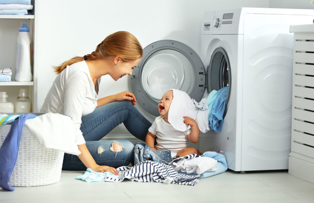 Mom and baby, sitting in front of the washing machine