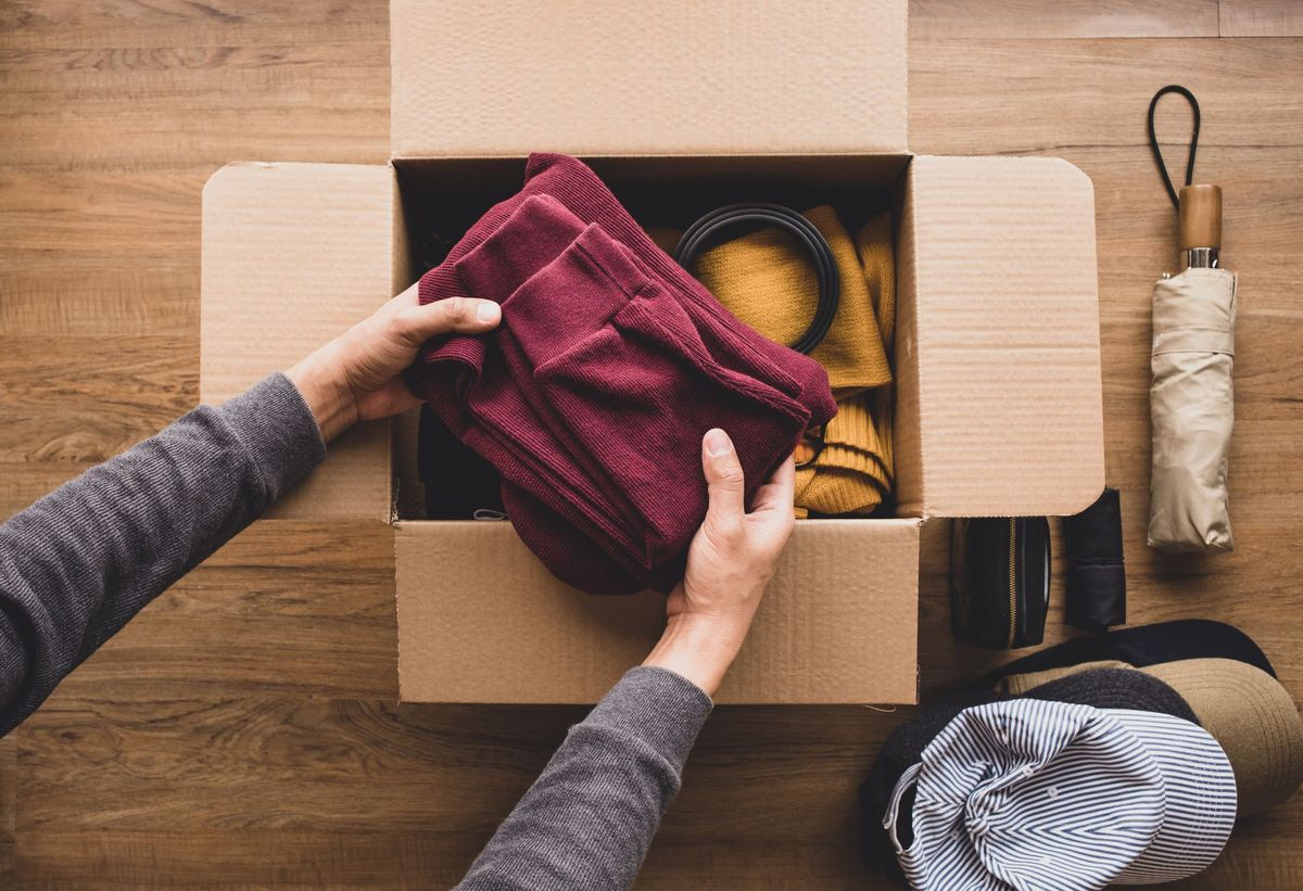 Man placing a sweater in the package