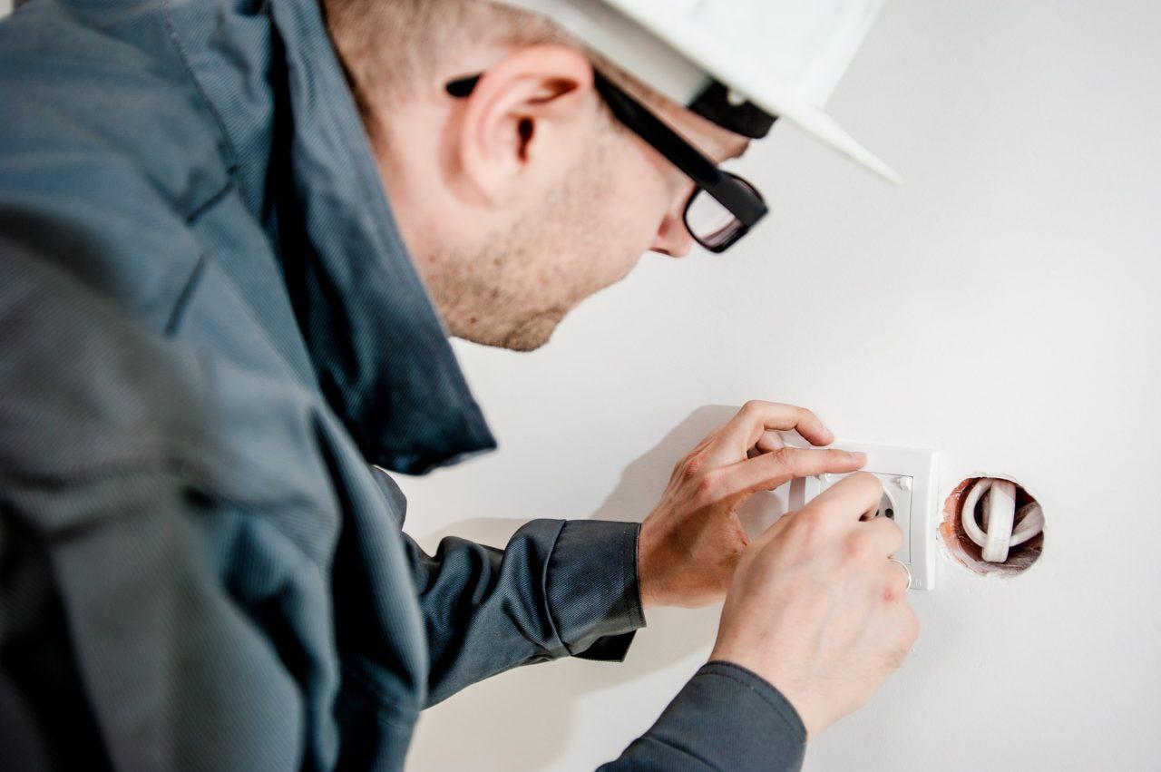 An electrician repairing an electric socket