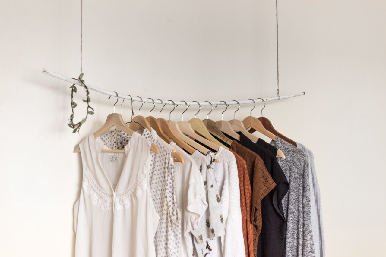 Rack of clothes in front of a white wall