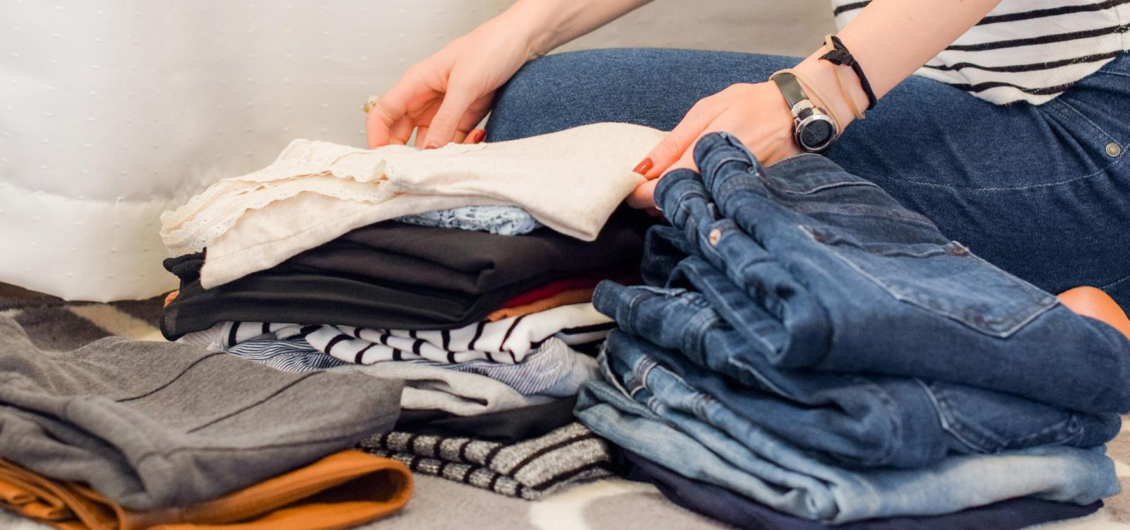 Woman folding T-shirts and jeans on the bed